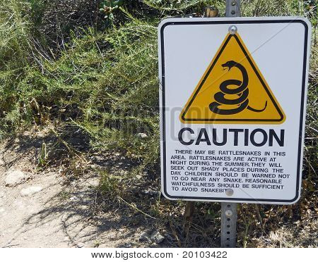 A Caution Sign warns of the Danger of Rattlesnakes along a Hiking Trail.